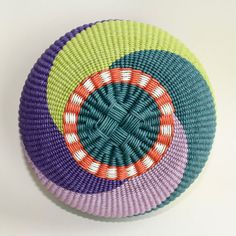 Mardi Gras (2016)  This basket is made with 1mm teal, purple, lavender, lime, orange and cream waxed cotton cord.  The basket begins with a simple circle of teal cord twined around a square formed by crossing the spokes. To complete the base a border using a stacking pattern with orange and cream has been added.  A simple spiral pattern using teal, lavender, purple and lime is used to create the basket's design.  The stacked border used on the base of the basket is then repeated on the top…