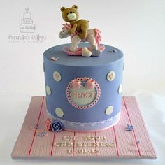 Rocking Horse Teddy Bear Christening Cake. Handmade Fondant ribbon roses, Pink floorboard cake cake board. Hand made Teddy Bear cake topper riding a rocking horse.