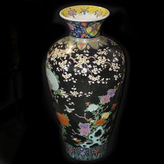 DESCRIPTION: Palace Size porcelain famille verte vase. Features hand enameled depicitions of an array of beautiful soaring birds, blooming flowers, and trees blossoming with flowers in hues of light blue, fuscia, orange, yellow, lavender, and turqoise. Finished with a black background and gold trim and polish. Marked on the bottom in blue Chinese letters. CIRCA: 19th-20th Ct. ORIGIN: China DIMENSIONS: H: 37″ Diameter: (Neck): 11.25″ L: 18″