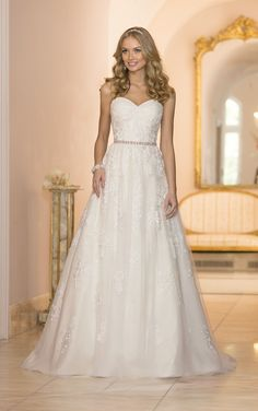 From the Stella York collection comes this vintage inspired Tulle A-Line wedding dress with Diamante-embellished Lace detailing. You'll love how the twist rushing accentuates the bust, while the beaded crushed Taffeta belt slims the waist. Beaded Lace and layered detailing is carried throughout the skirt into the traditional train. The beaded crushed Taffeta belt comes …
