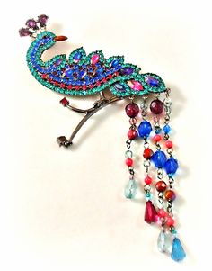 Avon Peacock Pin in jewel tone brilliant rhinestones and long beaded tail dangles created in 2004. 6 inch long bird brooch. Brilliant peacock colors make this a statement piece much desired.