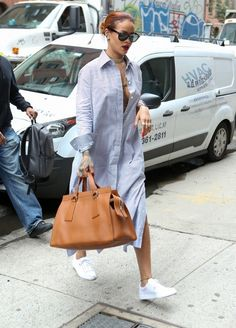 Rihanna wears a striped shirt dress with a tan leather tote, wayfarer sunglasses, and white sneakers