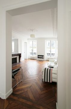 (-S- like the way the flooring is separated between the two rooms. Between the lower floor main room and two side rooms.  Parquetry floors with stark white walls. Perfection