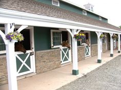 Beautiful barn, love the Dutch doors, stone, & hanging baskets horse stables Dream Stables, Dream Barn, Horse Barn Designs, Horse Barn Plans, Horse Ranch, Horse Property, Horse Stalls, Barn Stalls, Farm Barn