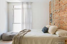 quarto aconchegante com parede de tijolinho e pufe perto da janela - matéria em parceria com a boobam.com.br