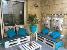 pallet setting against wall with colorful planter matching cushions