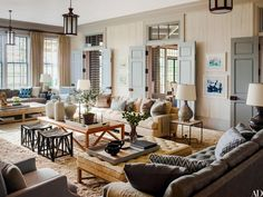 A trio of sofas designed by Steven Gambrel and manufactured by Dune anchor the living room. The bronze lanterns are by Vaughan, and the stools are by Michael S. Smith for Jasper.