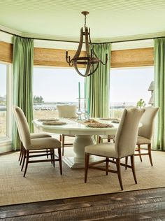 upholstered chairs, white pedestal, green linen window panels + woven shades
