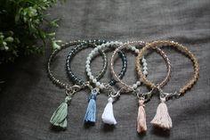 Bracciale sottile con perline metallizzate, perline sfaccettate in vetro, doppia in cotone annodata a mano.  Lunghezza nappine: 3 cm Disponibile