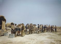 Air and ground crews of No 417 Squadron, Royal Canadian Air Force line up for bully and tea on a desert airfield in North Africa. May 1943.