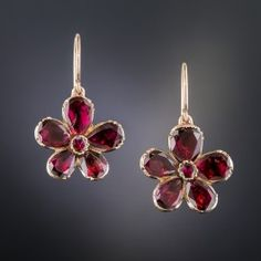 Early (circa mid-19th century) Victorian garnet earrings backed in 9k rose gold, hence of British origin. Each of the five petals are set with a pear shape almondine garnets. Wonderful wearable antique ear baubles. 5/8 inch, they drop a bit further from the new 14K ear wires.