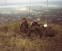 Russian soldiers, one of them wearing a WW2 German helmet, overlooking Grozny, 1999