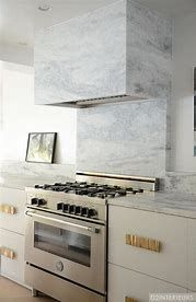 Contemporary kitchen features a white cabinets adorned with gold hardware topped with gray marble flanking stainless steel stove under a grey marble backsplash and a gray marble vent hood. White Marble Kitchen, White Kitchen Backsplash, Kitchen Hoods, Kitchen Countertops, Gray Marble, Backsplash Ideas, Marble Room, Kitchen Grey, Open Kitchen