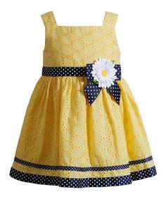 A dainty daisy adorns a polka dot bow over sunny hues, providing this breezy sleeveless silhouette with an adorable floral look.