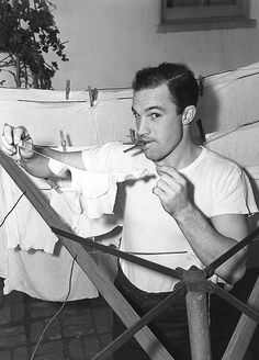 Gene Kelly hangs up his baby daughter's laundry, 1943