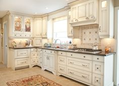 The glass doors and tile back splash suit the style of these glazed cabinets perfectly.
