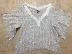 This is a very nice HD In Paris Anthropologie boho shirt women's size 4. The shirt is beige with a white floral print. There is crouched detail around the neck. The shirt has belle sleeve and is a shark bite.