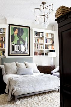 Built in bookshelves, shaggy fur rug, bold vintage art, and a statement making light fixture