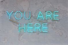 You Are Here neon using a world map as a background