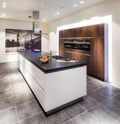 Een greeploze keuken met kookeiland bij Nuva Keukens. Een stijlvolle keuken dankzij de combinatie van de kleuren hoogglans wit en wildeiken bruin. Het ruime kookeiland zorgt voor voldoende werkruimte voor de hele familie. Een witte keuken in combinatie hout en met zwart keukenblad.