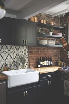 Ooh loving the brick, black cabinets and cool, tile backsplash. And a farmhouse sink is so great!