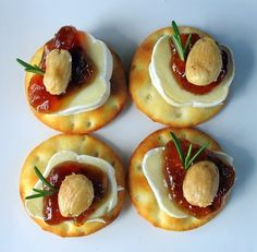 "Tiny brie bites - ingredients: 1 brie log, fig jam, Marcona almonds, pita crackers or any little-round cracker, and fresh rosemary for garnish. Directions: bring brie log to room temp, slice into 1/4"" thick slices."