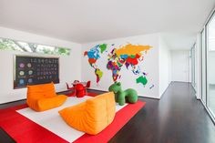 Contemporary playroom has a beautiful white and red border rug with two Togo Fireside Chairs placed on both ends of the rug. At the round play table are red Panton Junior Chairs placed in front of a metal framed chalkboard alongside a colorful world map on wall.