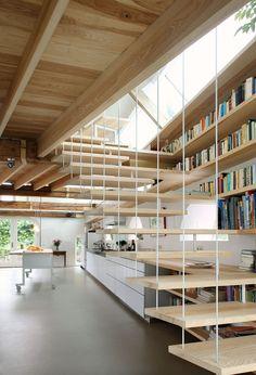 Immagine scala moderna in legno che si trasforma in un allestimento unico, diventando parte degli scaffali della libreria ma anche del top della cucina