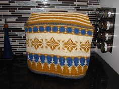 This pattern produces an appliance cover sized to fit a standard-sized stand mixer (e.g., Sunbeam Mixmaster, Hamilton Beach Classic or Kitchen Aid Classic). The cover is knit in the round from the bottom up and finished with a Kitchener bind off along the top. The stranded construction allows for an extra thickness of yarn to keep the cover stiff enough to hold its shape over the mixer. This pattern is a sister design of Granny's Fair Isle Tea Cosy.