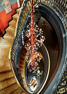 THE STAIRCASE IN MY NEW HOUSE IN BEVERLY HILLS.  THERE ARE FIVE IRON AND LUCITE CHANDELIERS, CONNECTED ONE FROMT HE OTHER, CASCADING DOWN THE LEAPARD CARPETED STAIR WELL TO THE BLACK GRANITE FLOOR BELOW.  recently photographed for Harpers Bazaar  by Christopher Sturman) - www.harpersbazaar.com/magazine/feature-articles/hutton-wilkinson-beverly-hills-home-0312#slide-2