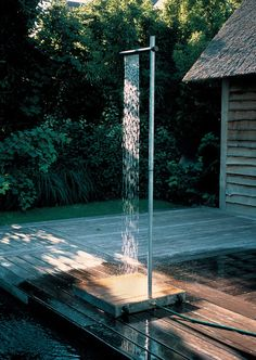 Outdoor Shower by TradeWinds Cascade is an outdoor shower for terraces and gardens made out of hot galvanised steel. The acacia wood base planks are comfortable and friendly to bare feet. A discreet tap on the vertical tube regulates the shower's pressure and the overhead horizontal tube provides a sheer waterfall curtain of water. It is easy to connect to a garden hose with a quick connector. via Tumblr