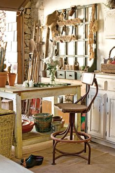 Tall worktable in this garden studio for potting plants, arranging cut flowers, and sorting fresh veggies. Old cabinets & baskets provide storage for gloves, spades, and other tools of the trade. <3