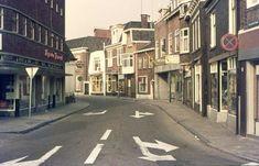 1976. Holtjesstraat. Links een wasserette met zelfbediening en kapper Frontroth. Rechts,  met witte uitbouw, automatiek-cafetaria Goossen. Rechts vooraan het onderdelenhuis van Stuivenberg.