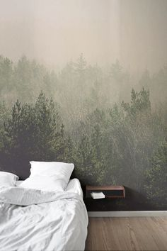 Looking for creative bedroom wallpaper ideas? This forest wallpaper design will make you want to get up in the morning. A hazy vintage filter casts a warm pinkish hue over this dreamy forest landscape. The sharp green and verticality of the pine trees in the forefront of this mural adds depth to your interiors.