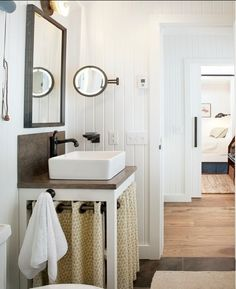 Not for the 60's ranch house, but I'm liking the basin-on-chunky-simple-table and the sink skirt hung on thick grommets.  Plus, all the white.