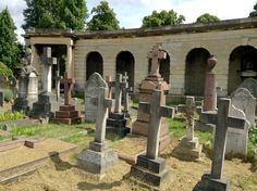 View of the numerous tombs in the circle of Brompton Cemetery, London, England, near the Chapel close to the south end.  Below the colonnades (seen in the background here) are catacombs which were originally conceived as a cheaper alternative burial to having a plot in the grounds of the cemetery. Unfortunately, the catacombs were not a success and only about 500 of the many thousands of places in them were sold.