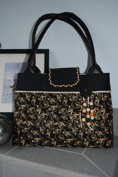 "My newest bag ""Jazzy.""  This custom order tote purse is in shades of black, gold, and cream.  The tassel includes hand made beads!  Fully lined with six interior pockets and soft padded handles, this bag is sure to please a music lover.  For more designs please see my Facebook page at Bobbin My Thread."