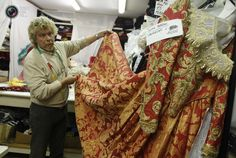 Costume designer Stefano Nicolao adjusts a dress in his atelier in downtown Venice February 6, 2012. Nicolao is one of the biggest costume designer in Venice with more than 10,000 costumes, working with theater, cinema and renting during the Venice carnival. REUTERS/Tony Gentile