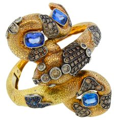 "A. Codognato Sapphire Color Diamond & Gold Snake Bangle Bracelet.  Hand engraved signature of maker.   Stunning snake bangle bracelet created by  Venetian designer Attilio Codognato. It is made of 18k yellow gold and set with three cushion cut sapphires and colored natural diamonds. The bracelet sits in the middle of the forearm.  The snake's head is 1"" wide in its widest point.  Sensational!"