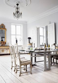 Love the perfectly gold accents and Parisian-inspired furniture in this all-white traditional dining room.