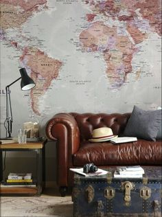 Industrial decor with classic leather couch, vintage chest table, and a world map as wallpaper.