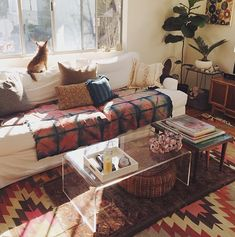 Boho sitting room, lucite coffee table, white sofa