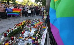 Warsaw residents stand next to flowers, rainbow flags and lit candles in front of the U.S. Embassy in Warsaw, Poland, Monday, June 13, 2016, in a sign of mourning for the victims of the deadly shooting in a U.S. nightclub in Orlando, Florida, that left many people dead, including the attacker and more than 50 injured. Deputy Chief of the U.S. Mission, John C. Law thanked those gathered for their gestures of sympathy.(AP Photo/Czarek Sokolowski)/XCS160/16165653714741/1606132025