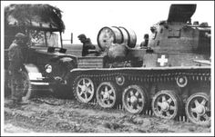 A Hungarian Toldi tank provides a pull to disabled Botond truck on a muddy road somewhere on the Eastern front.