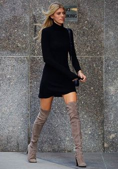 Devon Windsor wears a black minidress with a shoulder bag and neutral suede thigh-high boots