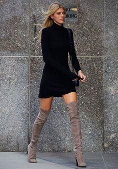Encantador conjunto de vestido negro con botas color gris encima de las rodillas.