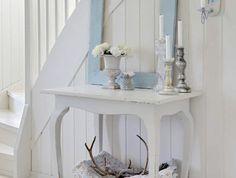 hall d'entrée maison en bleu pastel et en blanc avec un cadre qui sert de décoration sur une table peinte en blanc