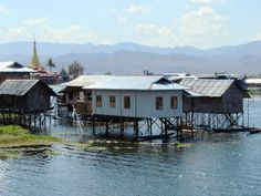 The ancient Alodaw Pauk Pagoda is just visible to the left in this photo of Nanpan village at the south end of Inle Lake, Myanmar (Burma). Inle Lake, Cabin, Mountains, House Styles, Travel, Home, Viajes, Cabins, Traveling