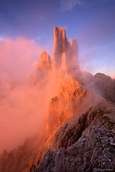 Brilliant sunset light illuminates the Vajolet Towers in the Rosengarten as misty clouds swirl off the peaks. Photo © copyright by Jack Brau...