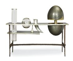 FRANCOIS-XAVIER LALANNE (1927-2008). Perhaps a bit decoesque? But commissioned by Yves & Pierre in 1965 (However, it only bears Yves' name). THE 'YSL' BAR, 1965 In maillechort and brass, two tiered, the upper tier with an ovoid bottle-rack in metal set in motion by a counterweight mechanism, with a horn-form shaker, a spherical ice bucket and a cylindrical crystal glass vase by the Cristalleries de Choisy-le-Roi, the vase passing through the two tiers, supported by four steel feet cut with a…